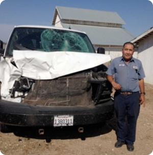 Man standing beside wrecked van